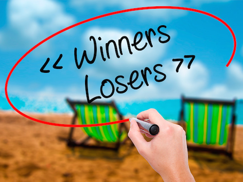 Man Hand writing Winners - Losers with black marker on visual screen. Isolated on sunbed on the beach. Business, technology, internet concept. Stock Photo